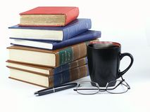 Books with Coffee. Stack of leather and hardback books with steaming coffee in mug, pen and glassess... ready to study Stock Images