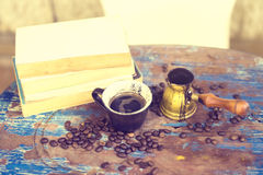 Books, coffee beans and a cup on an old table Royalty Free Stock Photos