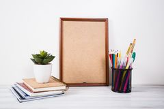 Books, colored pencils and painting canvas on the table.  royalty free stock photos