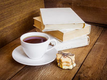 Books, cookies and cup of tea on wooden background Royalty Free Stock Photos
