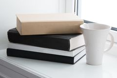 Books and cup in window. Books and cup arranged in white window Royalty Free Stock Photos