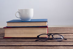 Books with cup of coffee and spectacles on wooden table. Against white background Royalty Free Stock Image