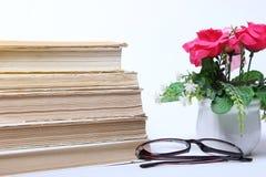 books den gammala bunten exponeringsglas och blommor i kruka Royaltyfri Fotografi