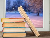 Books on the desk against the window with a winter landscape royalty free stock photography