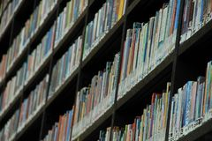 Books in different colours on the shelves in the library. Many books in different colours on the shelves in a part of the municipal library, Boekenberg in the Royalty Free Stock Images