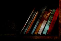 Books on dimly lit bookshelf. Dimly lit bookshelf with several weathered books Stock Photography