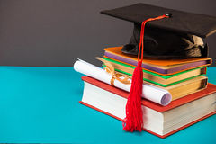 Books, diploma and graduation cap with tassel on blue with copy space. Education concept Stock Photography