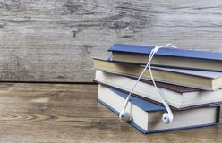 Books and earphone lay on wooden table. stock images