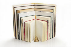 Books in expanded form with a bell. Stock Photography