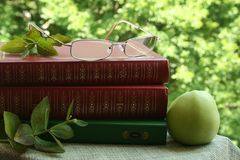 The books and  the eyeglasses and the green apple Stock Photo