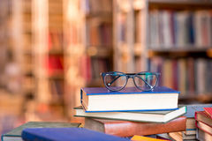 Books with eyeglasses at the library Stock Images