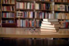 World of books. Books and eyeglasses on wooden desk in library, bookshelfs in background stock photos
