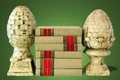 Books with Finials on Green Background. Stack of cloth bound books with finial bookends on a green background stock photography