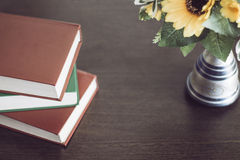 Books with flowers on a wood table. Three books with flowers on a wood table Royalty Free Stock Image