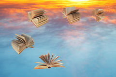 Books fly over sunset clouds Royalty Free Stock Photos