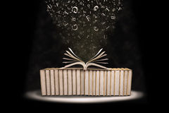 Books with flying letters. Stack of books with flying letters shot in studio Royalty Free Stock Image