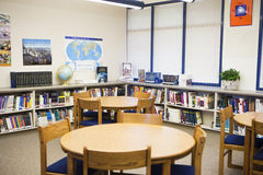 Books And Furniture Arranged In High School Library. Tables and chairs with books arranged on shelves in high school library royalty free stock images