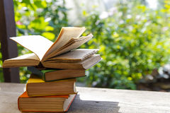 Books in  garden. Pile of books on an open fozduh on a bench in the garden. Close-up Stock Image