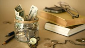 Books with glass penny jar filled with coins and banknotes. Tuition or education financing concept. Scholarship money. Savings for future education. Books stock video footage