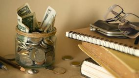 Books with glass penny jar filled with coins and banknotes. Tuition or education financing concept. Scholarship money. Savings for future education. Books stock footage