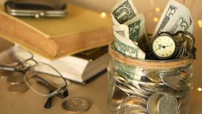 Books with glass penny jar filled with coins and banknotes. Tuition or education financing concept. Scholarship money. Savings for future education. Books stock video