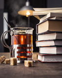 Books and a glass of tea with pieces of sugar on the table. Stock Photos
