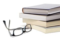 Books and glasses. Books and reading glasses on white background Stock Photo