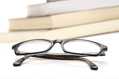 Books and glasses. Books and reading glasses on white background Stock Photos