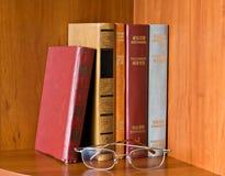Books and glasses on bookshelf Stock Photos