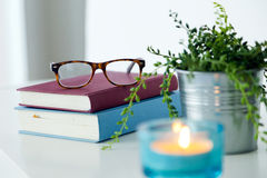 Books, glasses and candle on the night table. Stock Photos