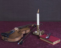 Books and glasses with candle and violin Stock Images