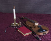 Books and glasses with candle and violin Royalty Free Stock Photos
