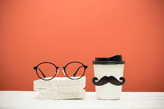 Books, glasses and cup with mustache Royalty Free Stock Photography