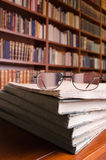 Books and glasses on library table. A shot of books and glasses on library table with a bookshelf in the background Stock Images