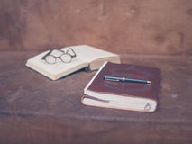 Books and glasses with a pen on sofa. A pen on top of a notebook with an open book and a pair of glasses in the background Royalty Free Stock Photography