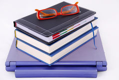 Books and glasses on top of laptop Stock Photography