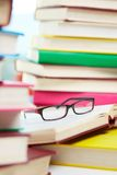 Books and glasses. Vertical image of eyeglasses lying over opened book in the library Royalty Free Stock Photo