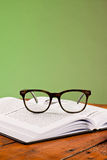 Books and glasses on a wooden table Stock Photos