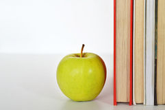 Books and a green apple Stock Photography