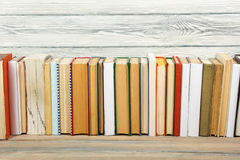 Books on grunge wooden table desk shelf in library. Back to school background with copy space for your ad text. Old Stock Photos