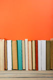 Books on grunge wooden table desk shelf in library. Back to school background with copy space for your ad text. Old royalty free stock photo
