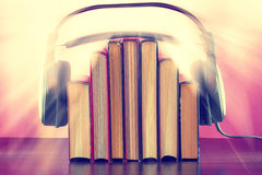 Books and headphones as an audiobook concept on a wooden table. On a pink background. The sun's rays create a joyful mood Royalty Free Stock Photography