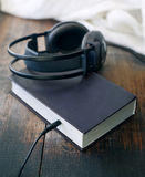 Books and headphones on wooden surface grunge. Stock Images
