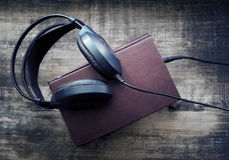 Books and headphones on wooden surface grunge. Stock Image