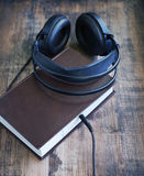 Books and headphones on wooden surface grunge. Stock Photos