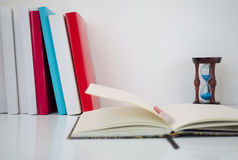 Books, hourglasses and open notebook on white table. Studying Stock Photography