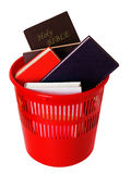 Books including bible in bin isolated over white Stock Photo