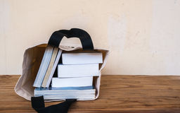 Books inside cloth bag on wooden table Royalty Free Stock Image