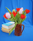 Books and jug of tulips. Pile of holiday books beside a brown jug filled with fresh  red and mauve tulips on a blue background Stock Photography