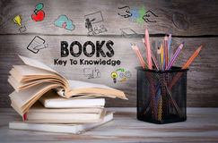 Books, key to knowledge. Stack of books and pencils on the wooden table. Royalty Free Stock Photography